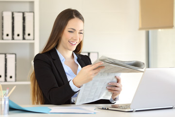 Happy executive reading a newspaper at office