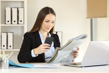 Executive reading newspaper and using phone