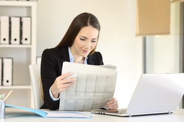 Businesswoman reading a newspaper at office