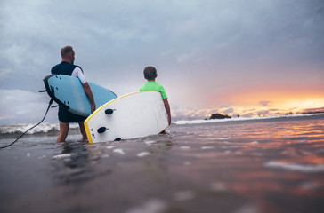 Father and son with surfboards preparing to surf at sunset