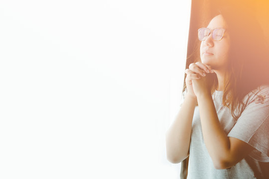 woman praying on the bed in the morning.teenager woman hand praying,Hands folded in prayer on the bed in the morning concept for faith, spirituality and religion