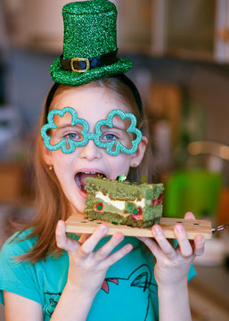 Irish girl with red hair in a green hat and sunglasses in the shape of a clover and laughing and eating green cake with raspberries