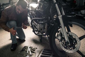 Young bearded man fixing bike