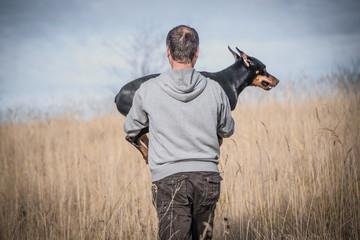 Owner holding his Doberman pinscher dog,selective focus