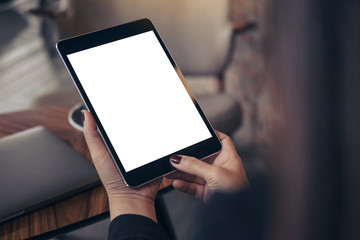 Mockup image of woman's hands holding and looking at black tablet pc with blank white desktop screen in cafe