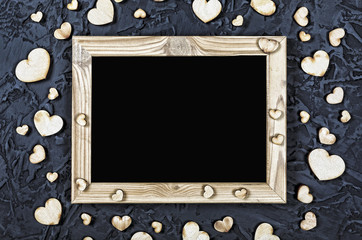 Valentine's Day. Layout for the postcard. Wooden frame blank and hearts on a black stone background