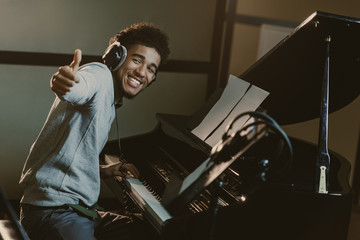 happy young piano player showing thumb up