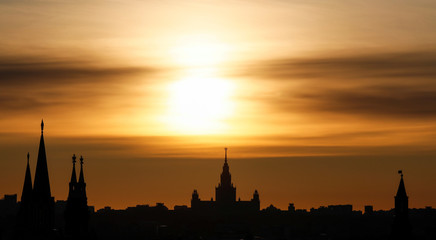 The sun sets over the main building of the Lomonosov Moscow State University and Kremlin towers in Moscow