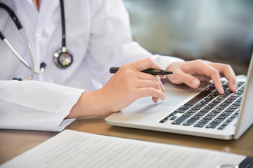 Female Doctor working with laptop.