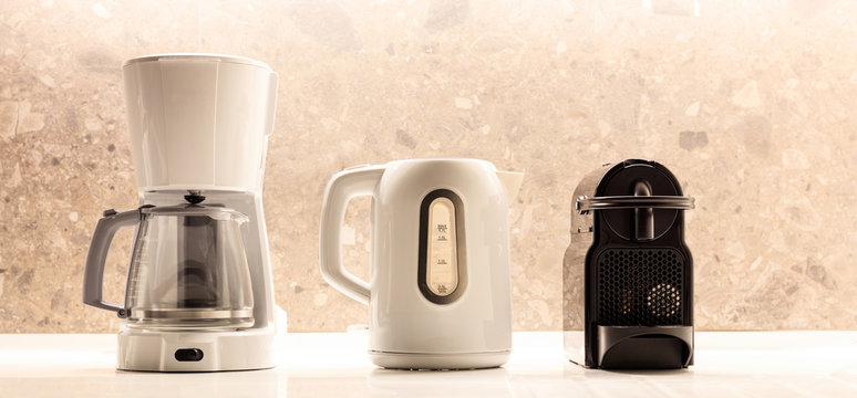 Kitchen small appliances on white surface. Colorful, blurred background. Close up view with details.