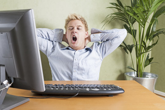 Tired man yawning when working in front of computer in office