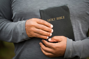 African American man holding a Bible.