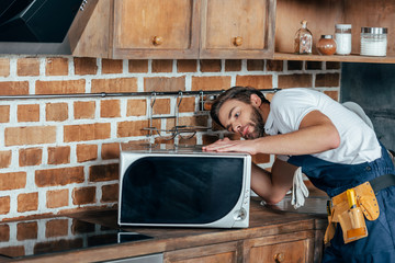 young handyman repairing microwave oven in kitchen