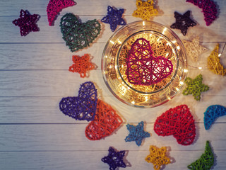 A woven red heart is inside a large glass ware on a light wooden background. From the bottom are wicker balls and a luminous garland. There are figures of stars and crescents around