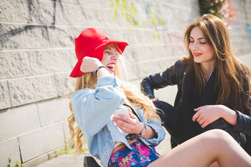 Two young blonde and brunette girls chatting