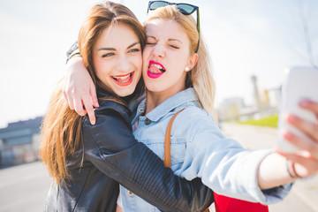 Youn beautiful blonde and brunette girl taking selfie