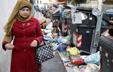 A woman walks next to garbage bins in Rome