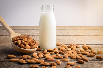 almond milk in bottle with Almonds pour from wood spoon