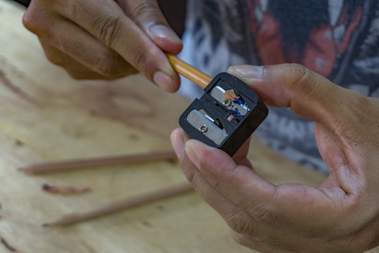 Man sharpening the pencil with pencil sharpener