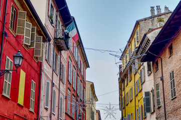 Colorful buildings in a street with Christmas decorations in Piacenza, Italy. HDR effect.