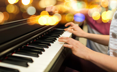 close up of woman hands playing piano over lights