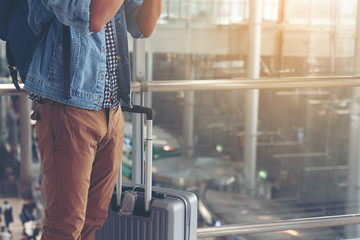 Young traveler man with carrying his rucksack and baggage standing and taking a photo in the airport upon arrival.