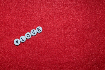 Love letter on a red background, letters in the form of plastic buttons with a sign hashtag