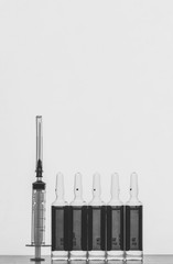 disposable syringe and ampoules with solution for injections on a grey background with space for text, black and white photo