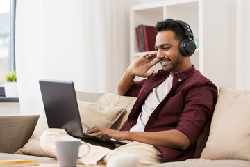man in headphones with laptop listening to music