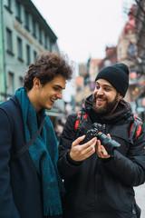 Cheerful men watching camera