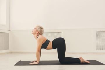 Young woman practicing yoga, Bitilasana exercise