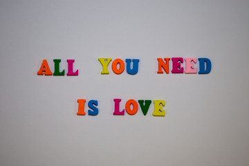 All You Need Is Love message from multicolor alphabet letters on white background