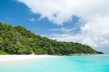 Beautiful clear sea with rock, white sand and fresh tree island with blue sky for rest and relax.