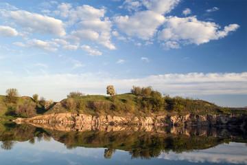 Весенний пейзаж с водоемом и облаками.