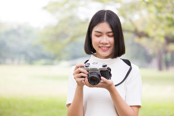 Attractive Asian shot hair woman holding retro camera with smiling, Woman using camera at outdoor place.
