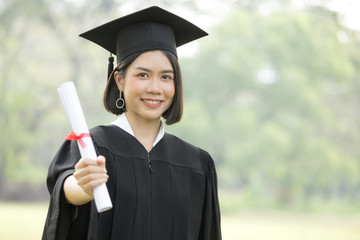 Young Asian Woman Students wearing Graduation hat and gown, Garden background, Woman with Graduation Concept.