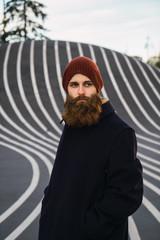 Bearded man standing on asphalt hill