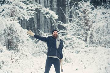 Bearded man with axe in snowy forest.