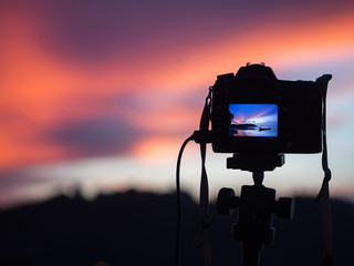 DSLR Camera capturing sunrise of beach view.Close up camera, background Landscape out of focus