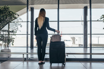 Rear view of slim young female traveler standing in airport terminal holding heavy suitcases looking through the window at airplane