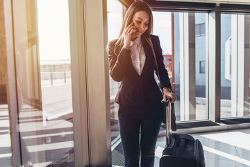 Smiling elegant woman walking with her baggage in airport talking on smartphone