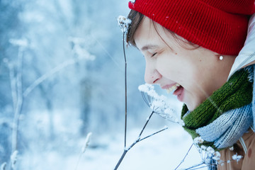 Outdoor closeup portrait of young beautiful girl smiling amid snowfall