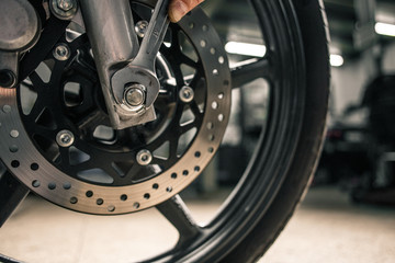 Close up of man's hand holding mounting wrench near the motorcycle's vehicle.