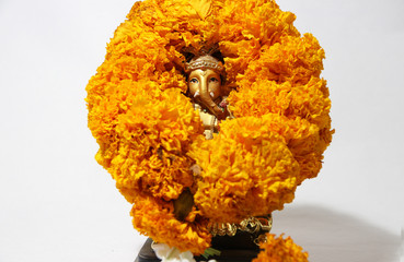 Mini Ganesha made from brass with garland yellow marigold flower and white background, the son of Uma Devi god in Hinduism and Brahmanism. God of knowledge and arts.