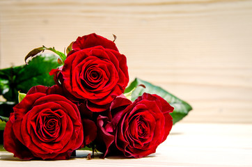 Three beautiful red roses lie on a wooden surface.