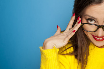 beautiful happy woman with glasses on blue background