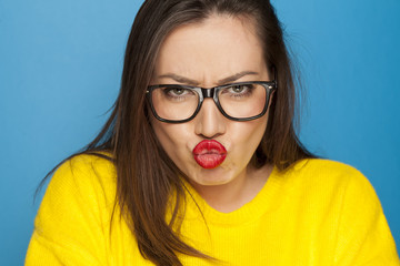 beautiful angry woman with glasses on blue background