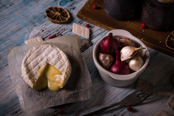 Hot camembert cheese on wooden board with garlic and onion