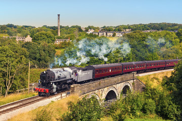 Railway bridge over river Worth near Oakworth, Yorkshire, England, UK