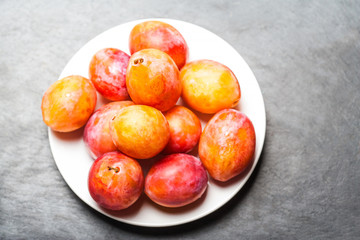 Fresh  red cherry plums on grey textured stone  background on white plate  with copy space